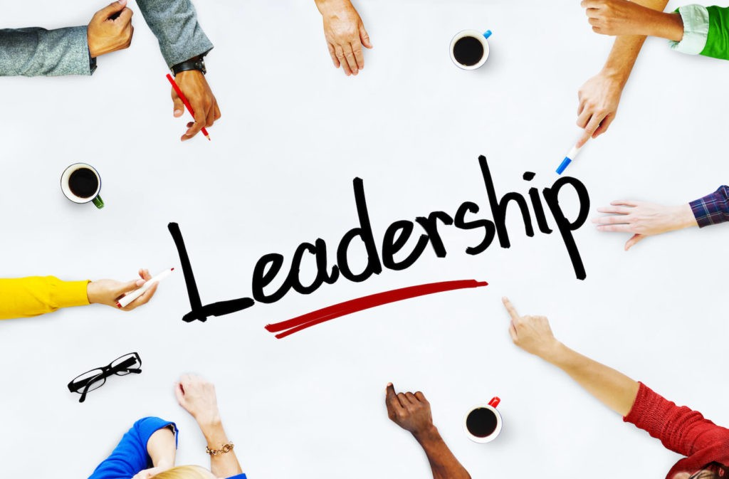 'Leadership' written on a white table surrounded by reaching hands.