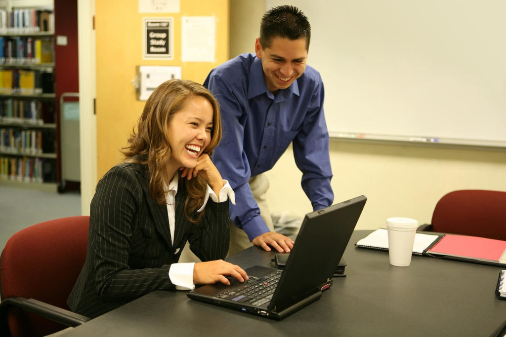 Two teachers laughing together while one uses a laptop.
