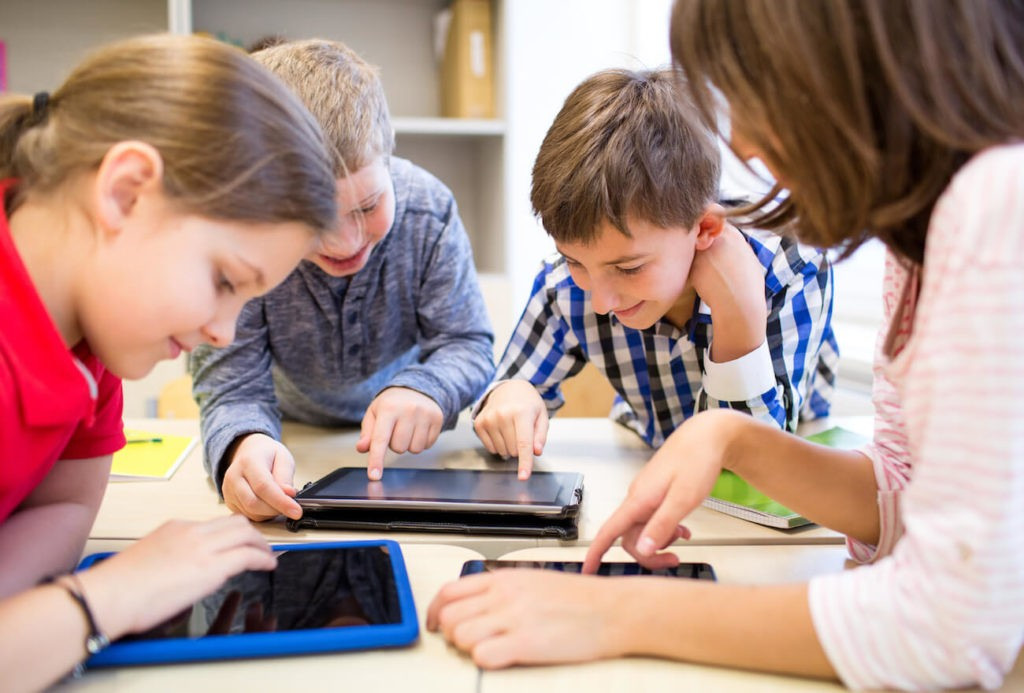 Young students sitting around a table using iPads.