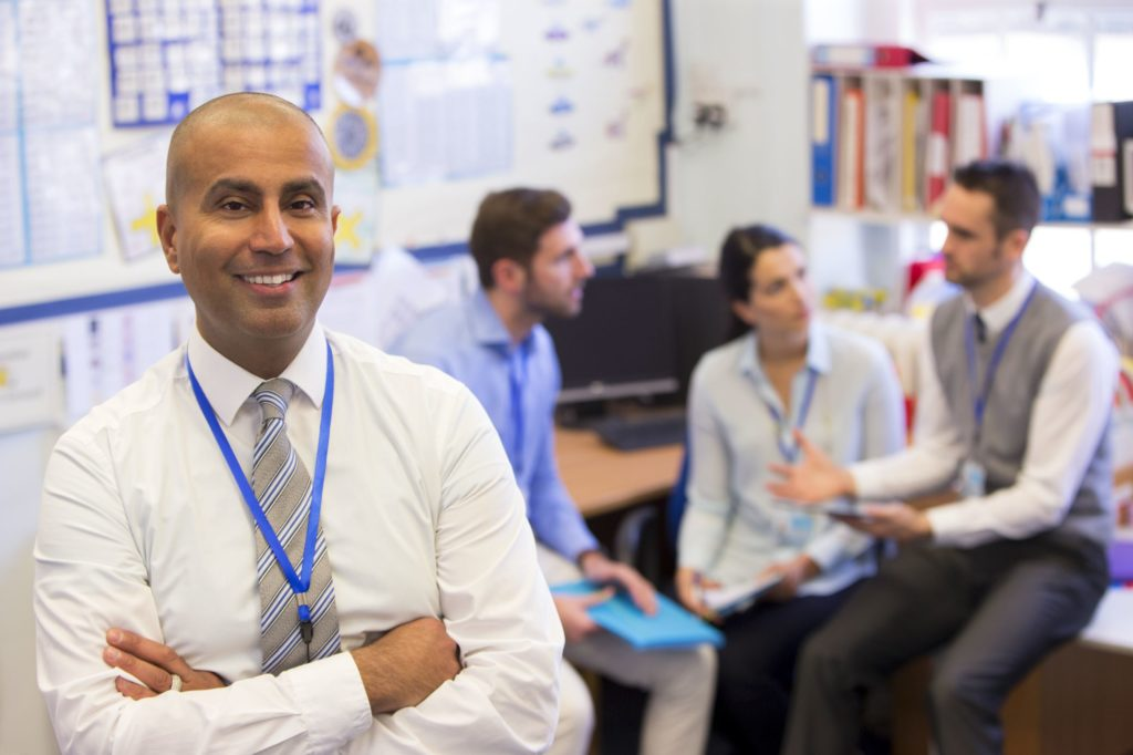 Male principal smiling with arms crossed in front of a group of teachers talking.