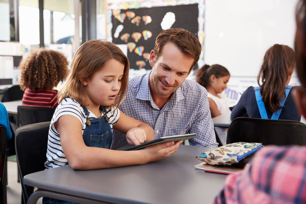 Young student sitting at a desk using a tablet with a male teacher kneeling next to her.