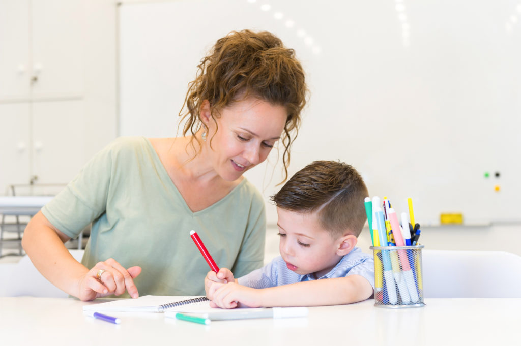 Teacher sitting with a young child coloring in a notebook.