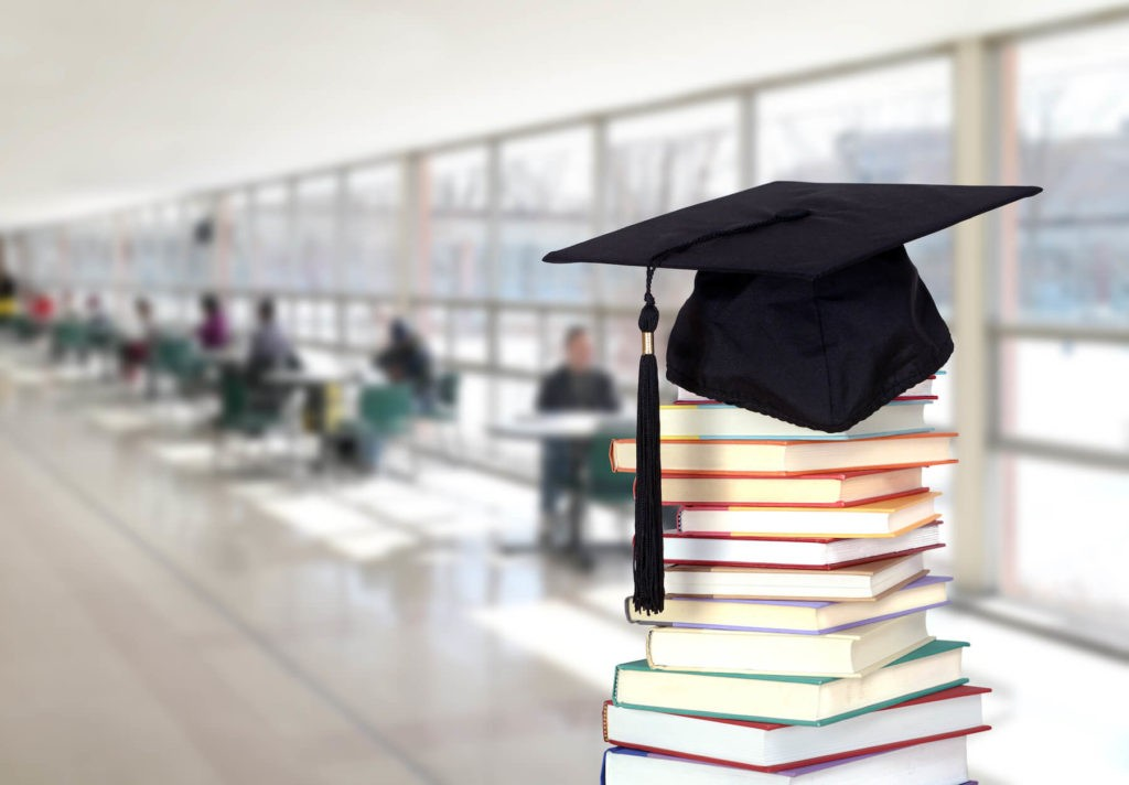 Graduation cap on top of a stack of books in a sunny hallway.