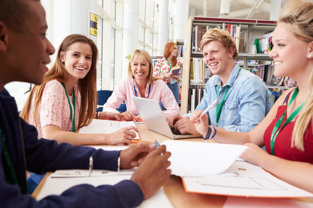 Group of young teachers sitting at a table working together in the library.