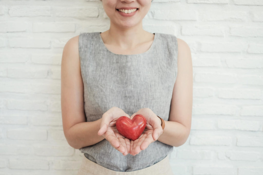 Smiling woman holding a red heart in her hands.
